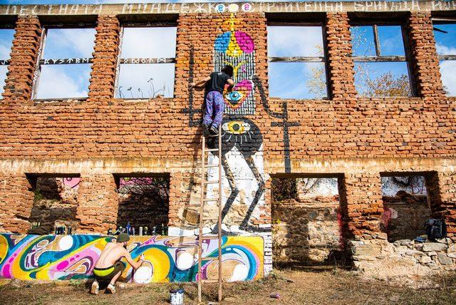 Kero Zen и Morgan Davy докато рисуват върху изоставена сграда.