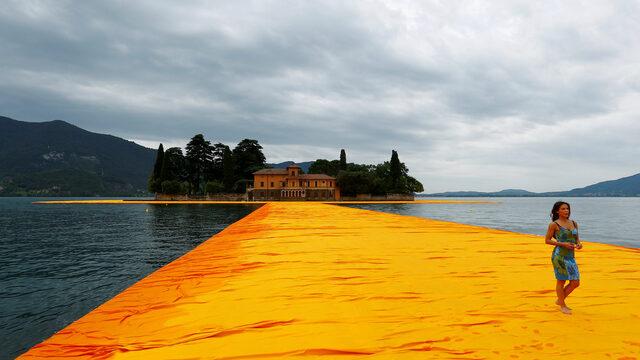 """Жена върви през """"Плаващите кейове"""" на Кристо на езерото Изео на 16 юни"""