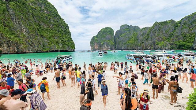 """Туристи се радват на белия пясък и тюркоазената вода в Мая бей в Тайланд. Това райско място стана известно на света от филма """"Плажът"""" (2000 г.) с Леонардо ди Каприо. В края на март 2018 г. дойде новината, че заливът ще бъде затворен за посетители в продължение на няколко месеца заради """"критично"""" увреждане на коралите. Местните власти обявиха, че планират ограничението за посещение на плажа от юни до септември да остане в сила и през следващите години."""