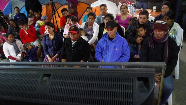 Емигранти, част от хилядите души от Южна Америка, които се отправиха към САЩ, гледат речта на президента