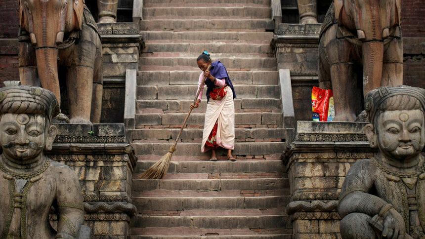 Жена мете предверията към храма Нятапола в Бхактапур, Непал